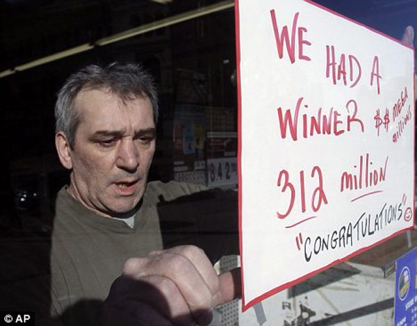 Store manager, Steve Gallucci, hangs a sign at Coulson's News in Albany