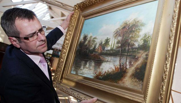 Tim Conrad from Wilfords Auctions holds the painting that could be an early Cezanne worth a fortune