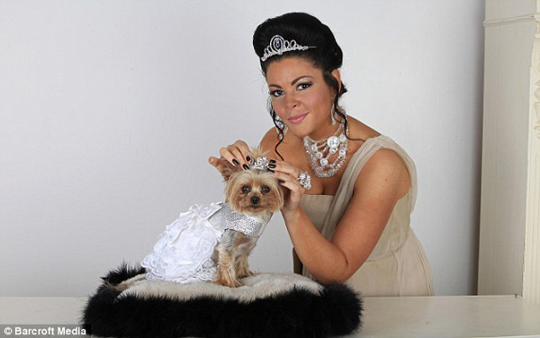 Louise Harris and her pet dog Lola pose for a photograph wearing their matching tiaras