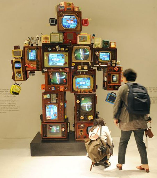 Visitors look at artwork by Paik Nam June entitled 'TV is Kitsch' at an auction preview in Hong Kong (AFP, Mike Clarke)