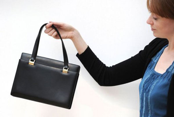 Christie's employee poses with a handbag owned by former British Prime Minister Margaret Thatcher