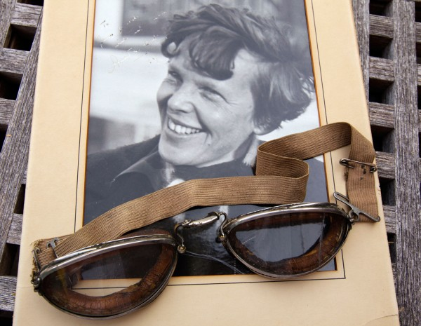 An original, unpublished personal photo of Amelia Earhart dated 1937, along with goggles she was wearing during her first plane crash