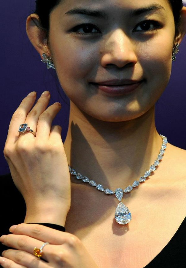 A model presents a 6.01-cart Cushion-shaped Fancy Vivid Blue Diamond and Pink Diamond Ring (top) and Mandarin Orange, a 4.19-Carat Fancy Vivid Orange Diamond and Diamond Ring sold (bottom)
