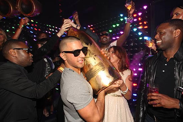 George Panayiotou and club waiters carry 30L double Nebuchadnezzar of Armand de Brignac Midas weighing a hefty 99lb