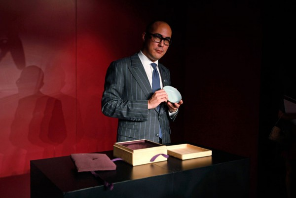 Nicolas Chow, Sotheby's Asia Deputy Chairman, holds the Chinese Song Dynasty ceramics Ruyao Washer at the Sotheby's auction in Hong Kong