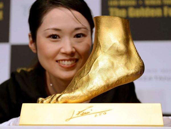 An employee of Ginza Tanaka poses beside the golden replica of football star Lionel Messi of Argentine's left foot 