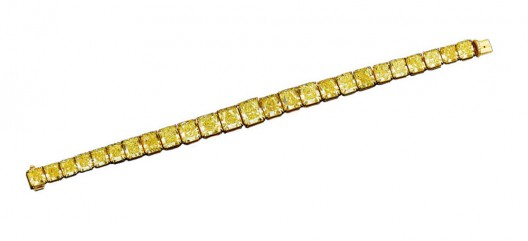 Twenty-five of the most beautiful, perfectly matched Natural Fancy Vivid yellow diamonds, totaling 55.66 carats, create a breathtaking golden glow in this incredible graduated bracelet